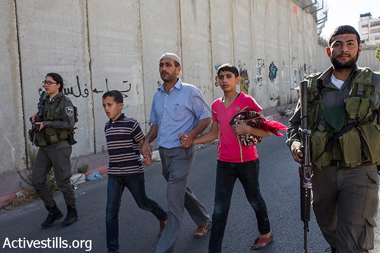 שוטרי מג״ב עוצרים פלסטינים לאחר שניתפסו מטפסים על חומת ההפרדה על מנת להשתתף בתפילות יום השישי השני של חודש הרמאדן במסגד אל-אקצא, בעיירה אל-ראם, ליד מחסום קלנדיה בין רמאללה וירושלים, 3 ביולי 2015. (יותם רונן/אקטיבסטילס)