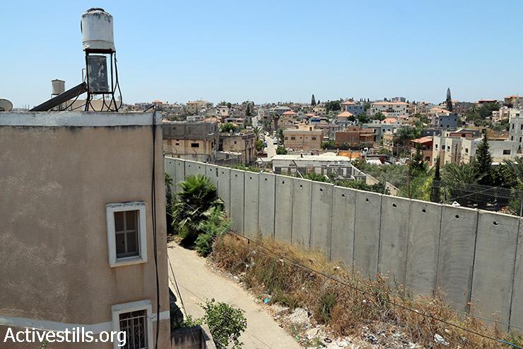חומת ההפרדה עוברת בין בתי בכפר נזלת עיסא (מימין) אשר בגדה המערבית והעיר באקה אל-גרבייה הנמצאת בתוך הקו הירוק (מהשמאל), 17 ביולי 2015. (אחמד אל באז/אקטיבסטילס)