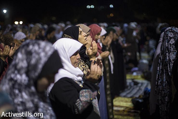 נשים פלסטיניות מתפללות במהלך ליילת אל-קאדר, מחוץ לכיפת הסלע במתחם מסגד אל-אקצא בעיר העתיקה בירושלים, 13 ביולי, 2015.   (פאיז אבו רמלה/אקטיבסטילס)