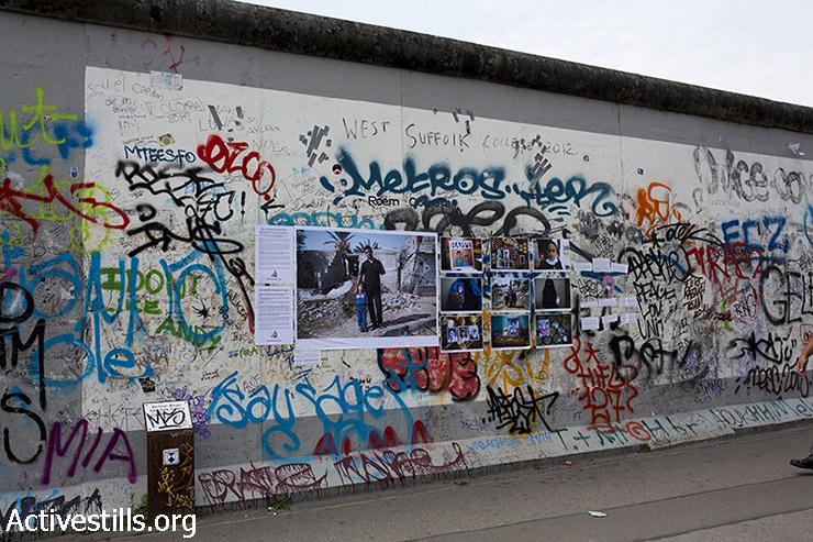 """תערוכת הרחוב """"משפחות שנמחקו (#ObliteratedFamilies) של קולקטיב אקטיבסטילס תלוייה ב״East Side Gallery״ על חומת ברלין ההרוסה, ברלין, גרמניה, 12 ביולי 2015. תערוכת הרחוב היא חלק מקמפיין המציין שנה להתקפה הישראלית בעזה ומציגה תמונות של משפחות שניספו במהלכה. (אן פאק/אקטיבסטילס)"""