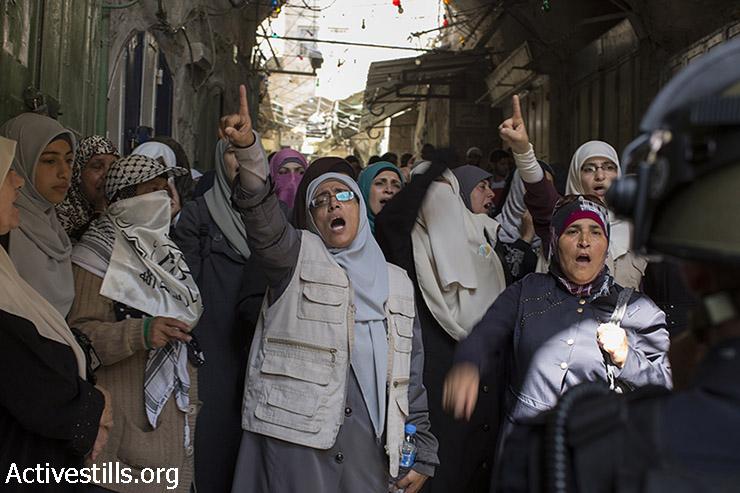 נשים פלסטיניות צועקות סיסמאות מול כוחות משטרה ישראליים במהלך הגבלת כניסה של פלסטינים למסגד אל-אקצא בעיר העתיקה של ירושלים, 26 ביולי 2015. במהלך הבוקר התרחשו עימותים בין המשטרה לפלסטינים אשר התבצרו בתוך המסגד בעקבות הודעת פעילי ימין קיצוני על כוונתם לעלות ביום ט' באב ולבנות את בית המקדש. העימותים התפשטו לעיר העתיקה והמשטרה סגרה את הסמטאות המובילות למסגד בפני פלסטינים. (פאיז אבו רמלה/אקטיבסטילס)