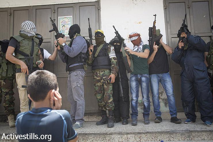 חמושים פלסטינים רעולי פנים מניפים את כלי הנשק שלהם במהלך הלוויתו של מוחמד אבו לטיפה במחנה הפליטים קלנדיה ליד רמאללה, הגדה המערבית, 27 ביולי 2015. אבו לטיפה נורה ונהרג בעת שנמלט דרך הגג על מנת להמנע ממעצר בעת פשיטה צבאית. (אורן זיו/אקטיבסטילס)