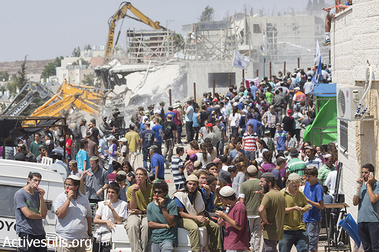 כוחות משטרה ומתנחלים עומדים סמוך לדחפורים בזמן הריסת ״בתי דריינוף״ בהתנחלות בית אל, צפונית לרמאללה, הגדה המערבית, 29 ביולי 2015. המבנים, הממוקמים על אדמה פלסטינית בבעלות פרטית, נהרסו תחת פסיקת בג״צ. (אורן זיו/אקטיבסטילס)