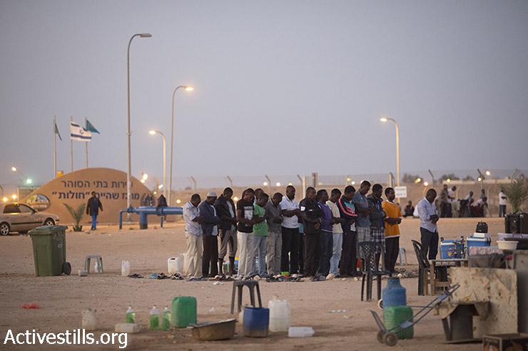 מבקשי מקלט אפריקאים הכלואים בבית המעצר חולות מתפללים לאחר אכילת ארוחת האיפטאר, ארוחה מסורתית לשבירת הצום בחודש המוסלמי הקדוש של הרמדאן, נגב, 5 ביולי 2015. (אורן זיו/אקטיבסטילס)