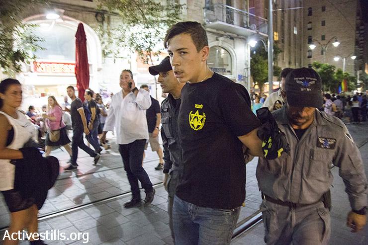 פעיל ימין עם חולצת להבה נעצר במהלך הפגנת זעם של פעילות להטב״ק בעקבות פיגוע הדקירה במצעד הגאווה בירושלים, שעות ספורות לפני כן, 30 ביולי  2015. (קרן מנור/אקטיבסטילס)