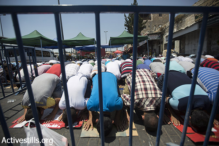 פלסטינים מוסלמים מתפללים מעבר למחסום משטרתי ברחובות מחוץ לעיר העתיקה בירושלים, 31 יולי 2015. המשטרה הגבילה את גיל הכניסה ואפשרה רק לגברים מעל לגיל  50 גישה למתחם מסגד אל-אקצא. ההגבלות באו בעקבות הצתת שני בתים פלסטינים בכפר דומא ע״י מתנחלים ישראלים, שבעקבותיה נשרף למוות תינוק בן 18 חודשים. (פאיז אבו רמלה/אקטיבסטילס)