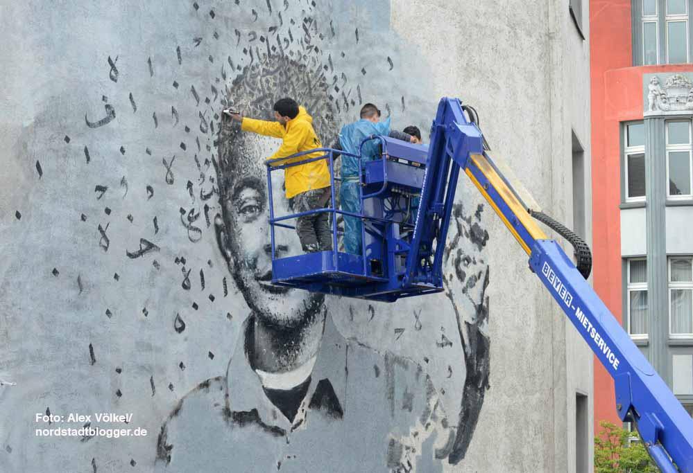 יאזן חלוואני וסטודנטים מקומיים מציירים בעזרת מנוף. צילום: אלכס פולק