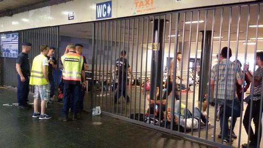 שוטרים נוספים עומדים בשער הכניסה לתחנת הרכבת הגדולה. אזרחים הונגרים ותיירים עוברים. את הפליטים השוטרים עוצרים  ומשאירים מאחורי הגדר (שחר שוהם)