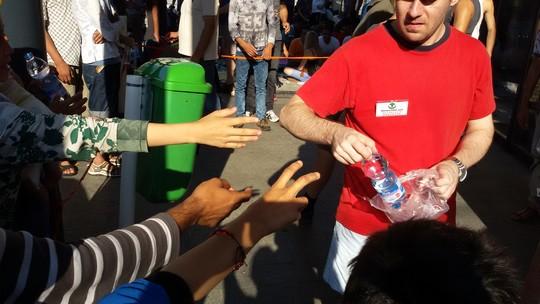"""אזרחים מתנדבים מקבוצת """"סיוע למהגרים"""" מחלקים מים ומזון למבקשי המקלט השוהים בתחנה המרכזית בבודפשט (שחר שוהם)"""