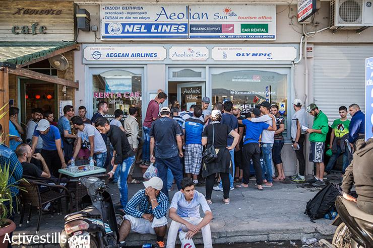 פליטים מחכים בתור לקנות כרטיס למעבורת שתיקח אותם מנמל מיטילנה לאתונה, לסבוס , יוון, 12 בספטמבר 2015.  (יותם רונן/אקטיבסטילס)