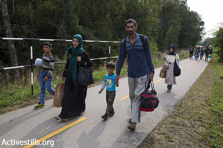 משפחת פליטים צועדת מעיירת הגבול ההונגרית הגשלום לגבול אוסטריה, במסעם למדינות מרכז וצפון אירופה. (קרן מנור/אקטיבסטילס)