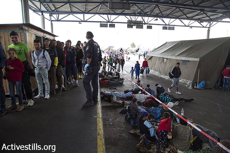 פליטים מחכים בתור לארוחה חמה, בעוד שאחרים נחים במחנה המעבר בגבול האוסטרי, 14 בספטמבר 2015. בעבר היה האזור מסוף גבול, אך לא היה בשימוש מאז בוטל הפיקוח בגבולות בין מדינות האיחוד האירופי. (קרן מנור/אקטיבסטילס)