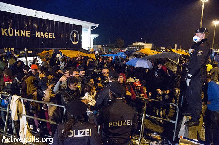 שוטר אוסטרי נותן הוראות לפליטים שנאספו במחנה המעבר בגבול האוסטרי, 14 בספטמבר, 2015. (קרן מנור/אקטיבסטילס)