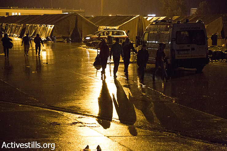 פליטים הולכים בגשם במחנה המעבר בגבול אוסטריה, 14 בספומבר 2015. (קרן מנור/אקטיבסטילס)
