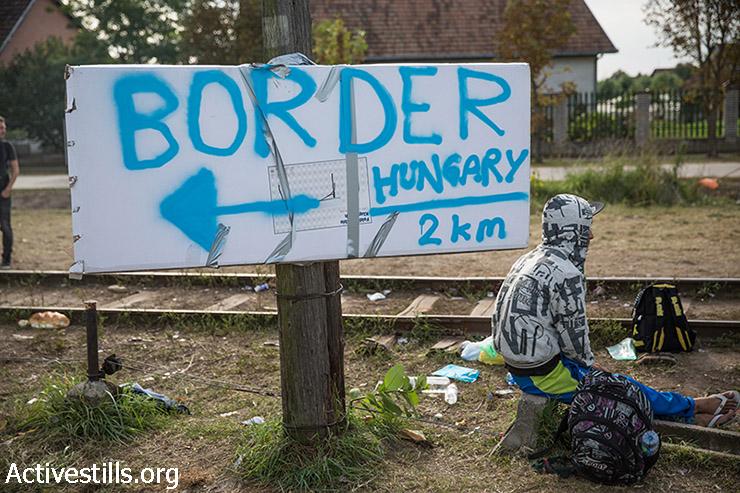 פליט נח ליד שלט המציין את הכיוון לגבול הונגרי בסמוך לגבול סרביה-הונגריה, 15 בספטמבר, 2015. ב -15 בספטמבר, לאחר שפליטים רבים חצו את הונגריה במסעם למערב וצפון אירופה, הונגריה סגרה את גבולה ולא איפשרה לפליטים להיכנס לתחומה. (יותם רונן/אקטיבסטילס)