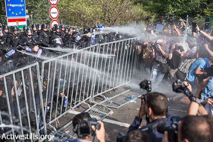 שוטרים הונגרים משתמשים בתרסיס פלפל במהלך הפגנה מול שער סגור בצד הסרבי של הגבול הסרבי-הונגרי, 16 בספטמבר, 2015. המשטרה ההונגרית השתמשה בגז מדמיע, תרסיס פלפל ותותחי מים כדי לפזר מעל אלף פליטים שהצליחו להפיל שער במעבר הגבול, ולהכנס לשטח ההפקר. (יותם רונן/אקטיבסטילס)
