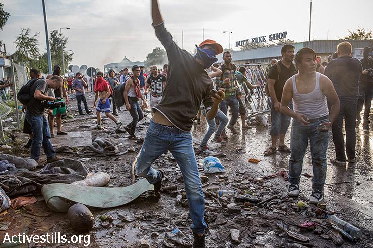 פליט זורק אבנים על שוטרים הנגרים במהלך מחאת פליטים מול הגבול הסגור, בצד הסרבי של גבול סרביה-הונגריה, 16 בספטמבר 2015. (יותם רונן/אקטיבסטילס)