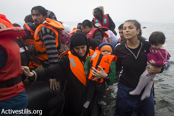 פליטים יורדים מסירת גומי תחת גשם אל חוף אפתלו, ממערב לנמל מיטילנה, באי היווני לסבוס לאחר שחצו את הים האגאי מטורקיה, 23 בספטמבר,2015. (אורן זיו/אקטיבסטילס)