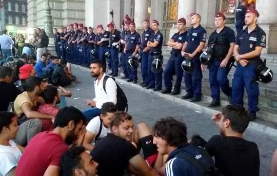 שוטרים עומדים בשורה וחוסמים את הכניסה לתחנת הרכבת בבודפשט. מולם יושבים פליטים (צילום: שחר שוהם)
