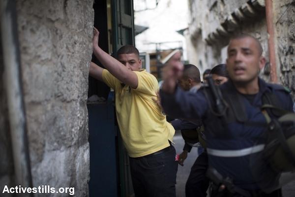 שוטר מעכב ומבצע חיפוש על גופו של צעיר פלסטיני בעיר העתיקה בירושלים. 12 באוקטובר 2015. (אורן זיו/אקטיבסטילס)