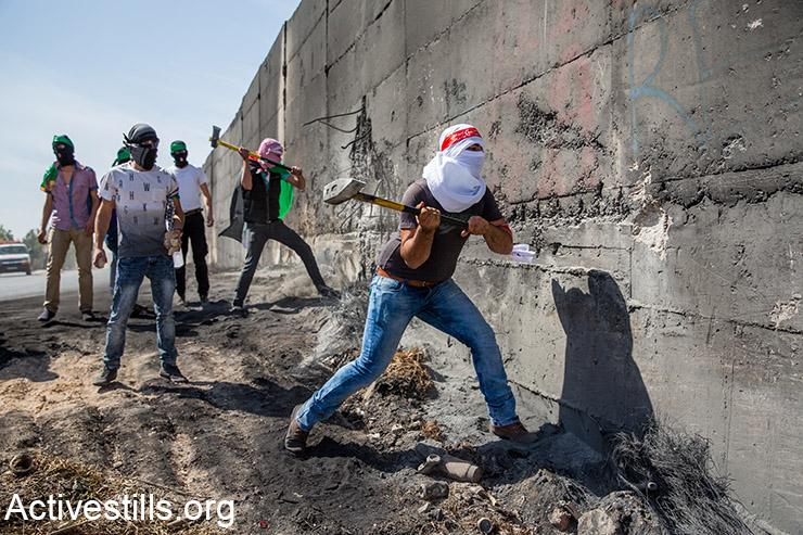 פלסטינים שוברים חלק בחומת ההפרדה במהלך עימותים עם כוחות ישראליים, באבו-דיס, מזרח ירושלים, 11 אוקטובר, 2015. (אקטיבסטילס)