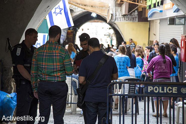 פלסטינים נבדקים מחסום משטרתי ברחוב הגאי בעיר העתיקה בירושלים, 12 אוקטובר, 2015. ברקע סוכת אבלים שהקימו מתנחלים בעקבות פיגוע הדקירה שהתרחש ברחוב ובו נהרגו שני אזרחים ישראלים.