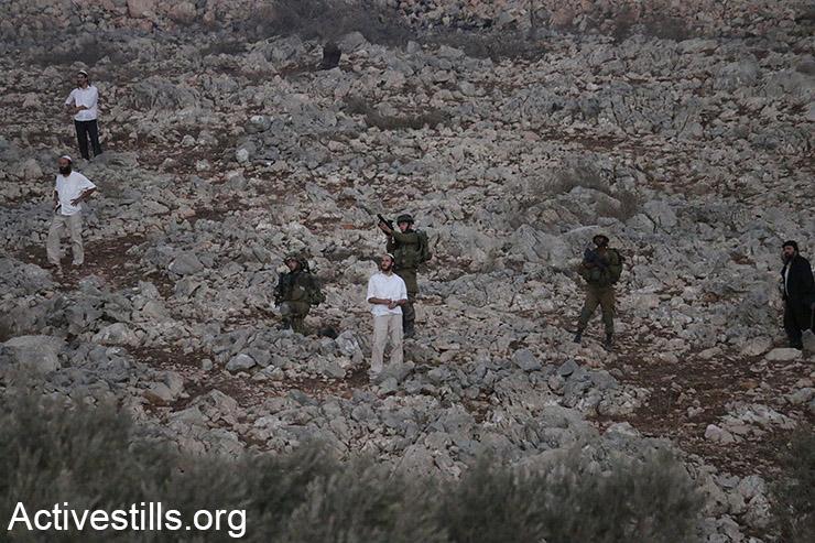 מתנחלים עומדים ליד חיילים בזמן עימותים שפרצו ליד הכפר בורין לאחר שמתנחלים הציתו שדות של חקלאים פלסטינים באזור, הגדה המערבית, ליד שכם, 3 אוקטובר, 2015. (אקטיבסטילס)