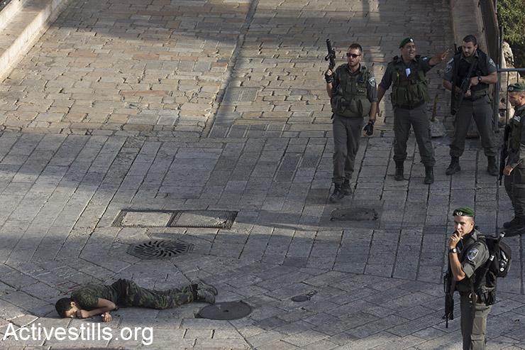 כוחות ישראלים עומדים ליד גופת פלסטיני שנורה במהלך מה שתואר כאירוע דקירה, העיר העתיקה, ירושלים, 14 אוקטובר, 2015. (אקטיבסטילס)