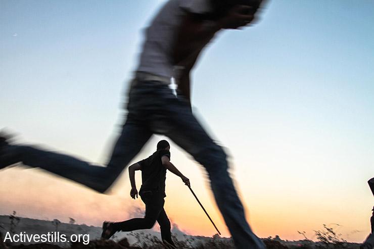 פלסטינים רצים מגז מדמיע במהלך עימותים במחנה הפליטים בוריג׳, רצועת עזה, 18 אוקטובר, 2015. (אקטיבסטילס)