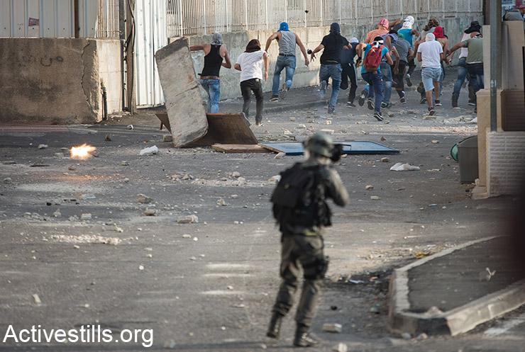 נערים פלסטינים רצים מירי של כוחות שיטור ישראליים במהלך עימותים בשועפט, מזרח ירושלים, 5 אוקטובר, 2015.