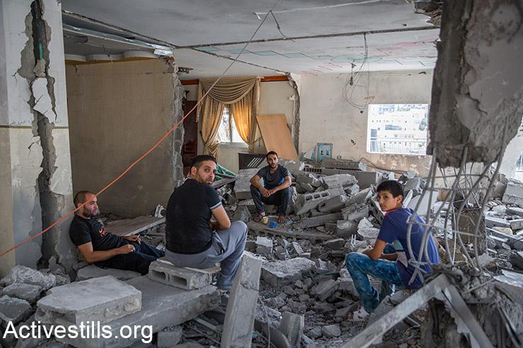 משפחתו של אבו ג׳אבאר יושבת על הריסות ביתם במזרח ירושלים, 6 אוקטובר, 2015.