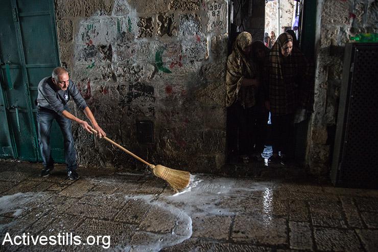 פלסטיני שוטף רחוב מכתמי דם לאחר מה שתואר על ידי כוחות ישראליים כאירוע דקירה, במהלכו נורתה אישה פלסטינית אשר זוהתה על ידי שוטר כתוקפת, העיר העתיקה, ירושלים, 7 אוקטובר, 2015. (אקטיבסטילס)