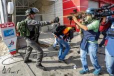 """שוטר מג""""ב מרסס עיתונאים וחובשים בגז פלפל, צומת בית אל 30 באוקטובר 2015. החובש אחמד נאסר בווסט הכתום נראה מתכופף (פאדי ערורי)"""