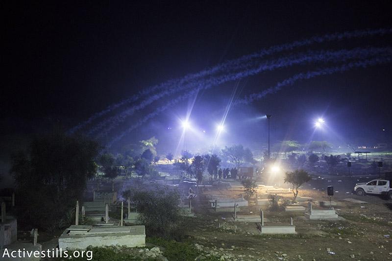 כוחות משטרה יורים גז מדמיע ופצצות תאורה במהלך הלוויתו של סמי אל-ג׳אר, בית הקברות ברהט, ישראל, ינואר 18, 2015. אורן זיו / אקטיבסטילס