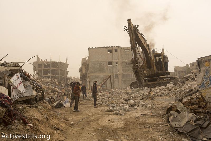 בולדוזר מנקה הריסות בתים בשכונת שג׳עיה, מזרח רצועת עזה, 11 פברואר, 2015. אן פאק / אקטיבסטילס