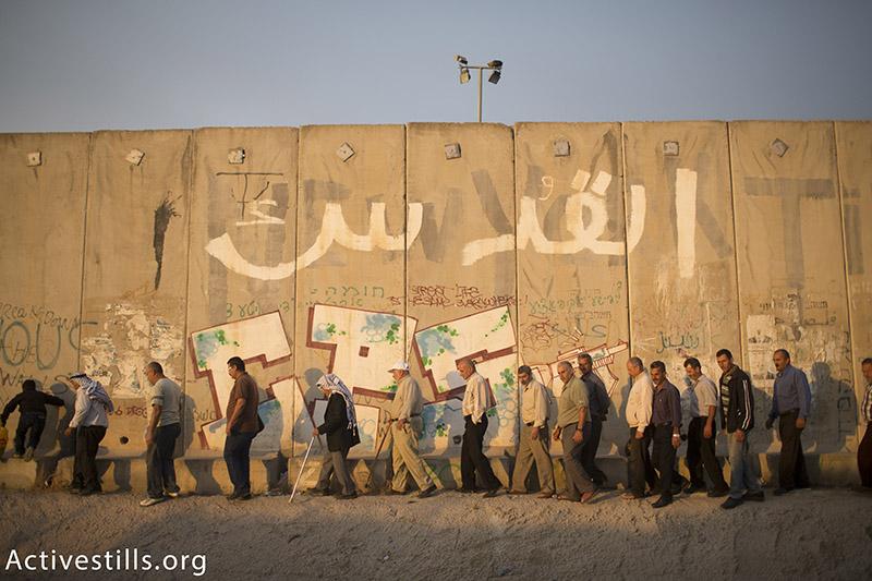פלסטינים צועדים ליד חומת ההפרדה הישראלית ליד מחסום קלנדיה, המפריד בין העיר רמאללה וירושלים, בדרכם להתפלל במסגדר אל-אקסה, רמאדאן, 26 יוני, 2015. יותם רונן / אקטיבסטילס
