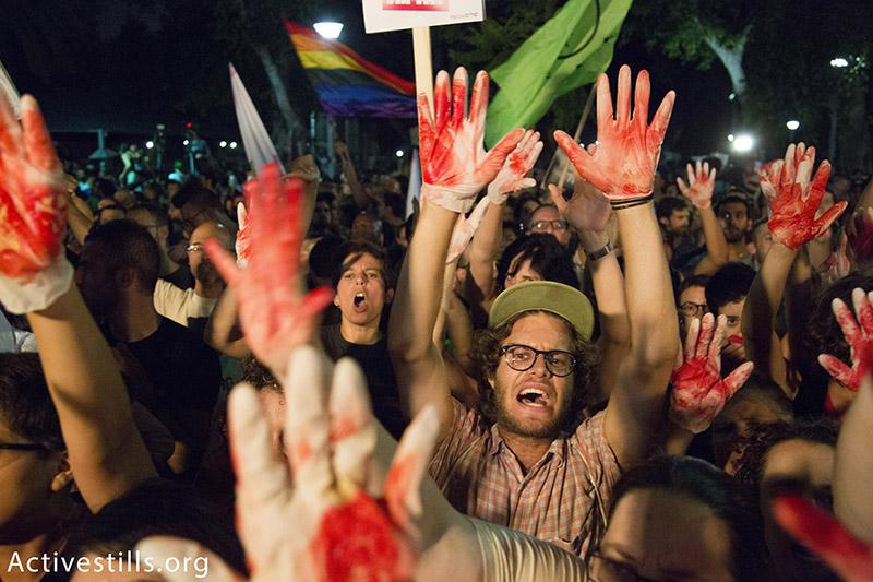 מפגינים מפנים ידיים צבועות באדום במהלך הפגנה נגד הומופוביה לאחר רצח שירה בנקי במצעד הגאווה, 1 אוגוסט, 2015. קרן מנור / אקטיבסטילס