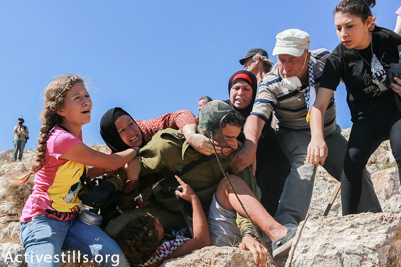 בני משפחת תמימי מנסים לעצור את מעצרו של הבן הצעיר במשפחה במהלך הפגנה לא-אלימה בכפר נגד הכיבוש, נבי סלאח, הגדה המערבית, 28 אוגוסט, 2015. מוחמד סאלים / אקטיבסטילס