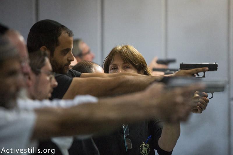אזרחים מתאמנים בנשק בחנות נשק, ירושלים, 15 אוקטובר, 2015. (יותם רונן / אקטיבסטילס)
