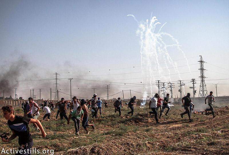 צעירים פלסטינים רצים מגז מדמיע שנורה על ידי הצבא הישראלי מהצד השני של הגבול באזור נחל עוז, רצועת עזה, 16 אוקטובר, 2015. עז זאנון / אקטיבסטילס