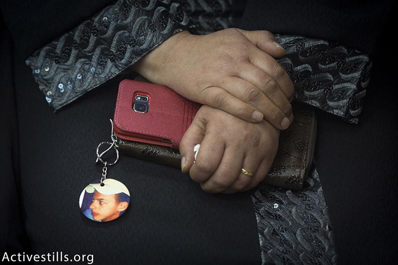 סוהא, אמו של הנער מוח׳מד אבו-ח׳דאר, מחזיקה את תמונתו, במהלך טקס לציון שנה להירצחו בשריפה על ידי יהודים, מזרח ירושלים, 30 נובמבר, 2015. אורן זיו / אקטיבסטילס
