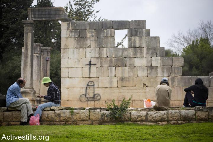 מטיילים בפארק על חורבות הכפר בירעם, וגרפיטי אנטי-נוצרי על שרידי כנסייה (אורן זיו / אקטיבסטילס)