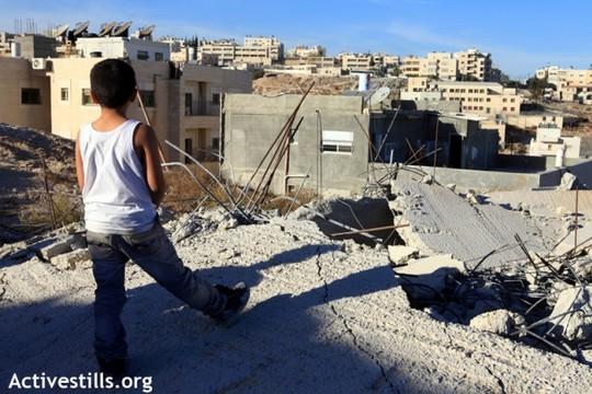 ילד פלסטיני עומד על בית שנהרס על ידי הרשויות בירושלים המזרחית (אן פאק/אקטיבסטילס)