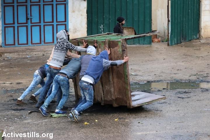 צעירים פלסטינים תופסים מחסה בזמן עימות על חיילים בקבטיה, 6 בפברואר 2016 (אחמד אל-באז/אקטיבסטילס)