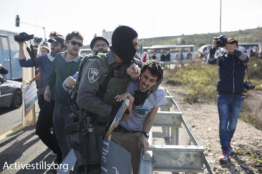 שוטר רעול פנים עוצר פעיל בלוחמים לשלום, מחסום המנהרות (אורן זיו / אקטיבסטילס)