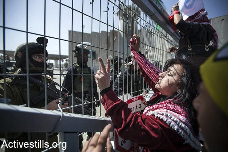 נשים פלסטינית צועקות ססמאות אל מול חיילים ישראלים במהלך הפגנה לציון יום האישה הבינלאומי מול המחסום הצבאי בקלנדיה, בגדה המערבית, 7 במרץ 2015. (אקטיבסטילס)