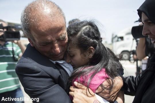 האסירה הפלסטינית הצעירה ביותר, רק בת 12, מתחבקת עם אביה לאחר ששוחררה מהכלא (אורן זיו/אקטיבסטילס)
