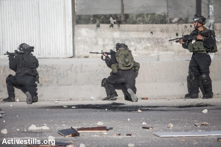 שוטרים יורים לעבר פלסטינים במחסום קלנדיה, 2014 (יותם רונן / אקטיבסטילס)