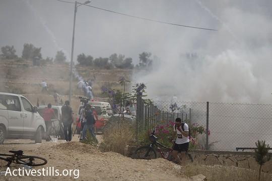 """כוחות הבטחון ירו גז לעבר המשתתפים ב""""רכיבת השיבה"""" לאחר שהגיעו עם אופניהם לנקודת הסיום בבלעין. 13 במאי 2016 (אורן זיו/אקטיבסטילס)"""
