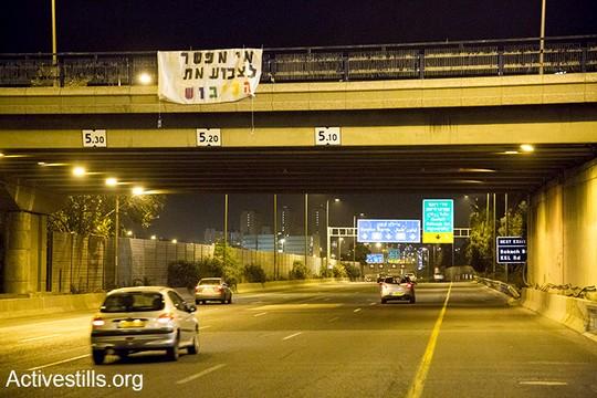 לקראת מצעד הגאווה פעילות ופעילים קווירים תלו בכניסות לתל אביב שלטים שמזכירים שהכיבוש כאן (קרן מנור/אקטיבסטילס)